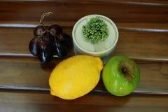 Frische nasse Früchte: Zitrone, grüner Apfel und Trauben mit der Dekoration lokalisiert auf hölzernem Hintergrund Lizenzfreie Stockfotografie