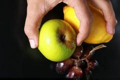 Frische nasse Früchte: Zitrone, grüner Apfel und Trauben mit der Dekoration lokalisiert auf schwarzem Hintergrund Stockfotografie