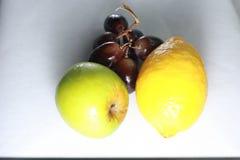 Frische nasse Früchte: Zitrone, grüner Apfel und Trauben mit der Dekoration lokalisiert auf weißem Hintergrund Lizenzfreies Stockfoto