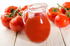 Frische nasse Tomate auf weißem Holz und Tomatensaft Lizenzfreie Stockfotografie