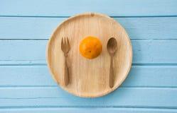 Frische Orange auf dem Teller hölzern lizenzfreie stockfotos