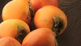 Frische orange Persimonen auf Holztisch stock footage
