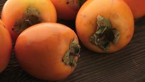 Frische orange Persimonen auf Holztisch stock video