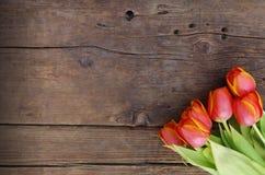 Frische orange Tulpen auf hölzernen Hintergrundbeschaffenheiten Lizenzfreie Stockfotos