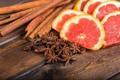 Frische Orange, Zimtstangen und Sternanis auf dunklem hölzernem Hintergrund Stockfoto