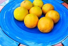 Frische Orangen auf blauer keramischer Platte Stockfoto