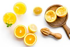 Frische Orangen der Pressung mit Juicer Orangensaft im Glas nahe halben geschnittenen Orangen auf Draufsicht des weißen Hintergru stockfotos