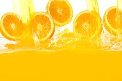 Frische Orangen, die in Saft fallen lizenzfreie stockfotos