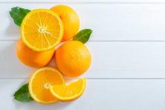 Frische Orangen und grüne Blätter auf weißem Holztisch Flach-Lage, Draufsicht stockfotografie