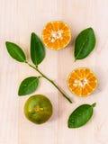 Frische Orangen und orange Scheibe auf hölzernem Hintergrund mit Orange Stockbilder