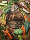 Frische organische Gemüsebestandteile für Suppe oder Suppe um rundes rustikales Ausschneidenbrett, Draufsicht Stockfotos