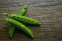 Frische organische grüne Erbsen auf einem woid Stockbild