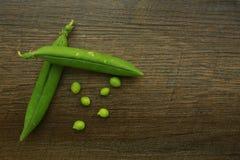 Frische organische grüne Erbsen auf Holz Stockbild