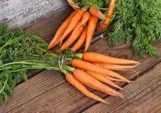 Frische organische Karotten auf hölzernem Hintergrund Lizenzfreie Stockfotos