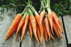Frische organische Karotten auf hölzernem Hintergrund Stockfotografie