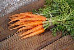 Frische organische Karotten auf Holztisch Lizenzfreie Stockfotografie