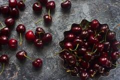 Frische organische Kirschen im Metall rollen auf dunklem Steinhintergrund Stockbild