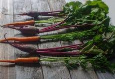 Frische organische rote Rübe und Karotte auf rustikalem hölzernem Hintergrund, gesunder Lebensstil, Herbsternte, rohes Gemüse, Dr Stockbilder
