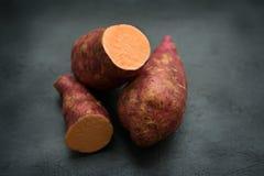 Frische organische Süßkartoffel auf dunklem Hintergrund stockbild