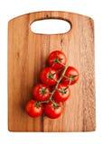Frische organische Tomaten auf dem hölzernen Brett lokalisiert auf weißem Hintergrund Lizenzfreies Stockbild