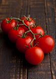 Frische organische Tomaten auf hölzernem Brett des Schmutzes Lizenzfreie Stockfotos