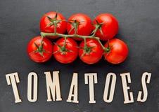 Frische organische Tomaten auf Steinbrett mit Buchstaben unten Lizenzfreies Stockfoto