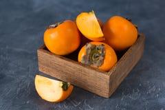 Frische Persimonefrucht in einer Holzkiste Schneiden Sie Frucht Abschluss oben stockfoto