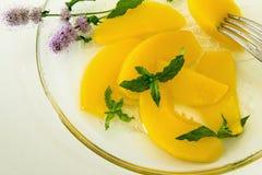 Frische Pfirsiche im Sirup mit Minze lizenzfreie stockbilder