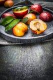 Frische Pfirsiche mit grünen Blättern in der Steinplatte auf dunklem Hintergrund Stockbilder