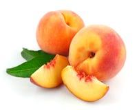 Frische Pfirsichfrüchte mit grünen Blättern Stockfoto