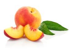 Frische Pfirsichfrüchte mit grünen Blättern Lizenzfreies Stockbild