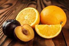 Frische Pflaumen und orange Frucht Stockfotos