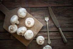 Frische Pilze auf der hölzernen Platte Lizenzfreies Stockfoto