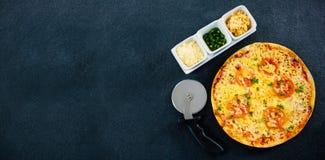 Frische Pizza durch Schneider und Gewürze auf Steinbehälter Lizenzfreie Stockfotografie