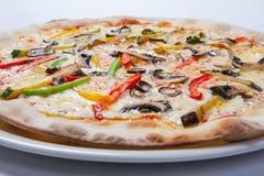 Frische Pizza mit Pfeffer, Käse und Pilzen auf weißer Platte stockfotos