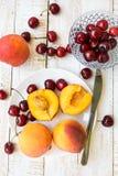 Frische reife bunte halbierte und ganze Pfirsiche auf weißer Platte, zerstreute süße Kirschen auf Plankenholztabelle Stockbilder