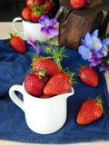 Frische reife Erdbeeren in einem keramischen Krug umgeben durch Pansies und Beeren Stockbild