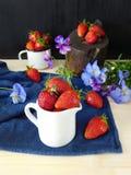 Frische reife Erdbeeren in einem keramischen Krug umgeben durch Pansies und Beeren Stockbilder
