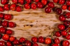 Frische reife Kirschen auf hölzerner Tabelle Beschneidungspfad eingeschlossen Lizenzfreies Stockfoto