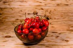 Frische reife Kirschen in der Glasschüssel auf Holztisch Lizenzfreie Stockfotografie