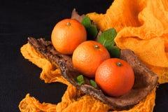 Frische reife Mandarinen mit Minze auf hölzerner Barke rollen, orange Gewebe auf schwarzem Hintergrund Moderne dunkle Stimmungsar Lizenzfreies Stockbild
