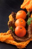 Frische reife Mandarinen mit Minze auf hölzerner Barke rollen, orange Gewebe auf schwarzem Hintergrund Moderne dunkle Stimmungsar Stockfoto