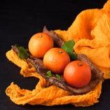 Frische reife Mandarinen mit Minze auf hölzerner Barke rollen, orange Gewebe auf schwarzem Hintergrund Moderne dunkle Stimmungsar Stockfotos