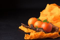 Frische reife Mandarinen mit Minze auf hölzerner Barke rollen, orange Gewebe auf schwarzem Hintergrund Moderne dunkle Stimmungsar Lizenzfreie Stockfotos
