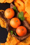 Frische reife Mandarinen mit Minze auf hölzerner Barke rollen, orange Gewebe auf schwarzem Hintergrund Moderne dunkle Stimmungsar Stockbild