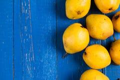 Frische reife organische yello Birnen auf blauem rustikalem Holztisch, natürlicher Hintergrund, Diätlebensmittel Stockbild