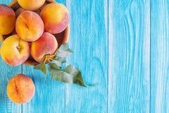 Frische reife Pfirsiche in einer hölzernen Schüssel auf einem blauen hölzernen Hintergrund Stockfotografie