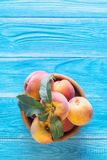 Frische reife Pfirsiche in einer hölzernen Schüssel auf einem blauen hölzernen Hintergrund Stockfotos