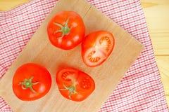 Frische reife Tomaten mit halfs auf hölzerner Tabelle Stockbild