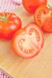 Frische reife Tomaten mit halfs auf hölzerner Tabelle Stockfoto